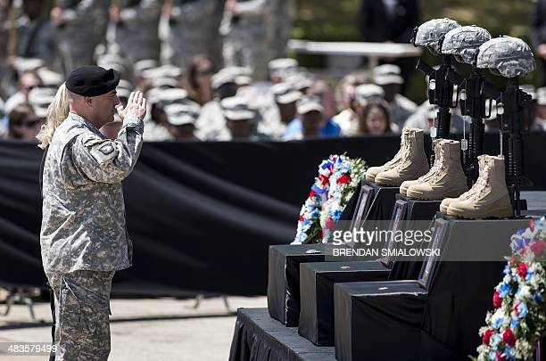 Army Lt General Mark Milley commanding officer of Fort Hood salutes memorials during a service at Fort Hood April 9 2014 in Texas Obama attended the...