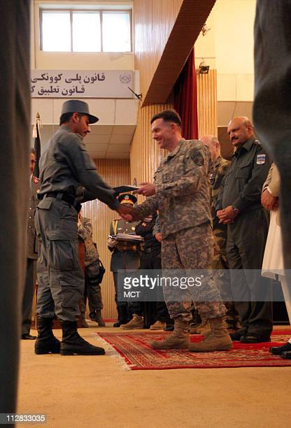 US Army Lt William B Caldwell who is in charge of training Afghan's security forces for NATO congratulates an Afghan officer as part of a ceremony on...
