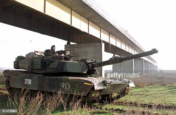 S Army M1A1 Abrams battlefield tank patrols 22 December next to the wardestroyed bridge that once linked the Croatian town of Zupanja with the...