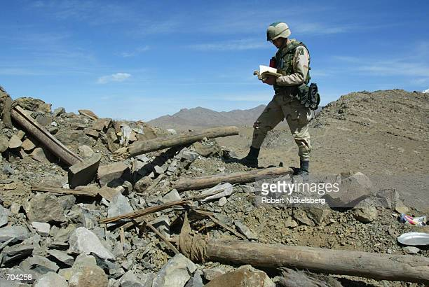 S Army Major Herndon of the 10th Mountain Division looks over an Arabic copy of the Koran in a bombed out al Qaeda position March 16 2002 in the...