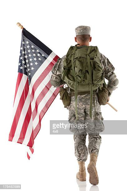 army man carrying an american flag - military flags stock photos and pictures