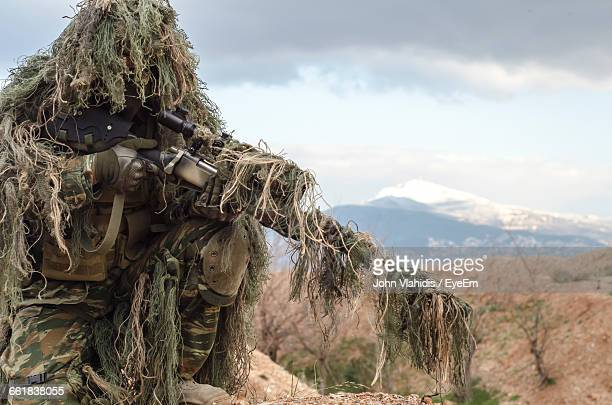 army man in ghillie suit with rifle on field - sniper imagens e fotografias de stock