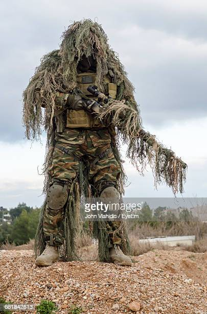 Army Man In Ghillie Suit With Rifle Standing On Field