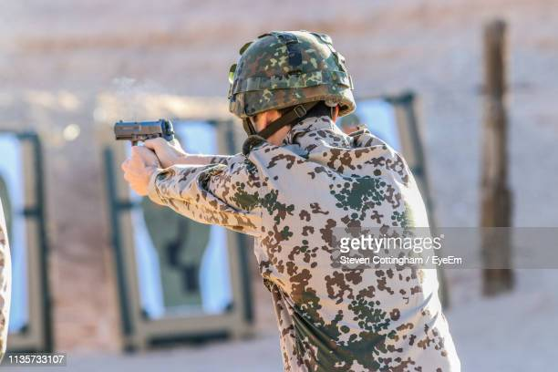 army man shooting with handgun against wall - steven cottingham stock-fotos und bilder