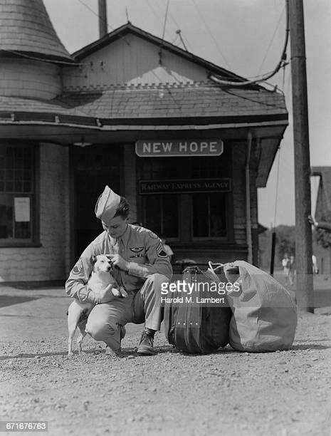 army man stroking and bidding goodbye near railway station - pawed mammal stock pictures, royalty-free photos & images