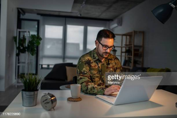 army man using laptop at home - army stock pictures, royalty-free photos & images