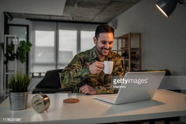 homme d'armée utilisant l'ordinateur portatif à la maison - professional occupation photos et images de collection