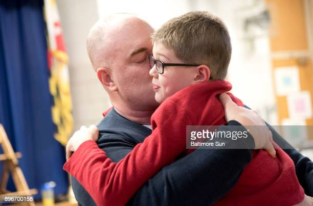 Army Master Sgt Thomas Pardue embraces his son Ebin Pardue after surprising him by returning early from an Army deployment in Korea at Millersville...