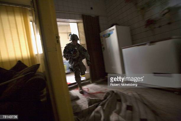 Army medic dashes from the kitchen area carrying a helmet in an abandoned apartment where SSGT Hector Leija 27 years was shot and critically wounded...