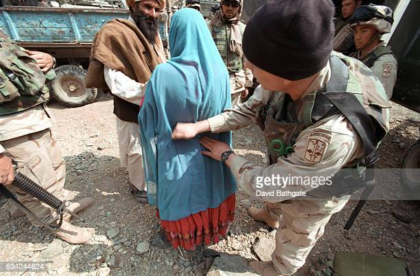 A US Army medic examines a village woman following a search of the area