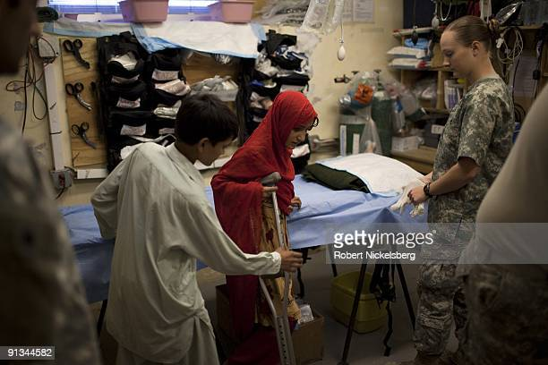 Army medic right prepares to clean and bandage the burned foot of a young afghan girl looks Forward Operating Base Blessing in Nangalam Afghanistan...