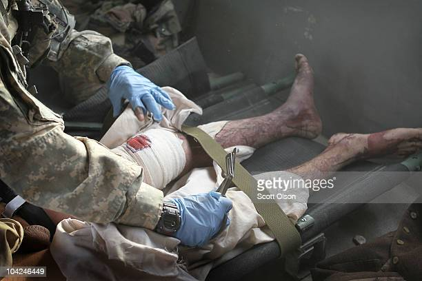 US Army medic SGT Tyrone Jordan of Charlotte NC attached to Dustoff Task Force Shadow of the 101st Combat Aviation Brigade works on a wounded enemy...