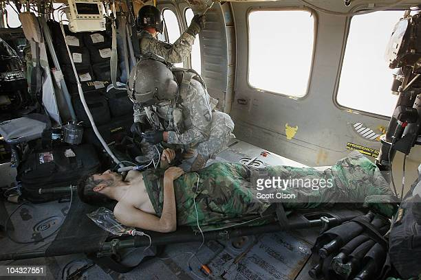 S Army medic SGT Tyrone Jordan of Charlotte NC attached to Dustoff Task Force Shadow of the 101st Combat Aviation Brigade works on an enemy prisoner...