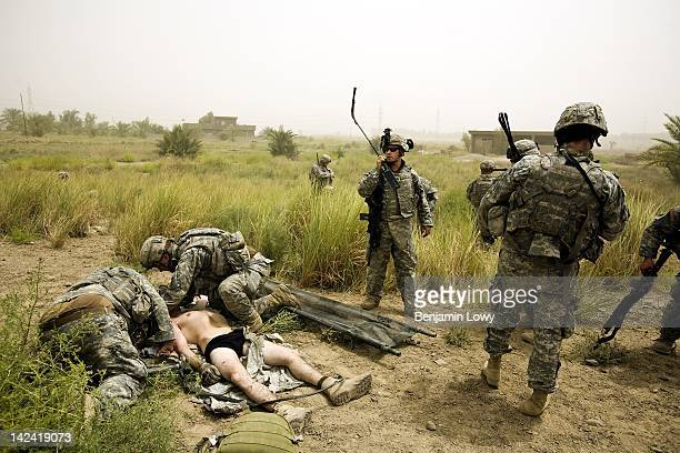 Army medics and soldiers treat a greviously injured US soldier after the humvee he road in and was positioned in the gu turret detonated an IED...