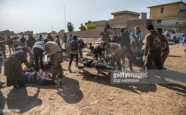 Army medics and volunteers attend to an influx of patients suffering a multitude of injuries at an Iraqi Special Forces 2nd division open air field...