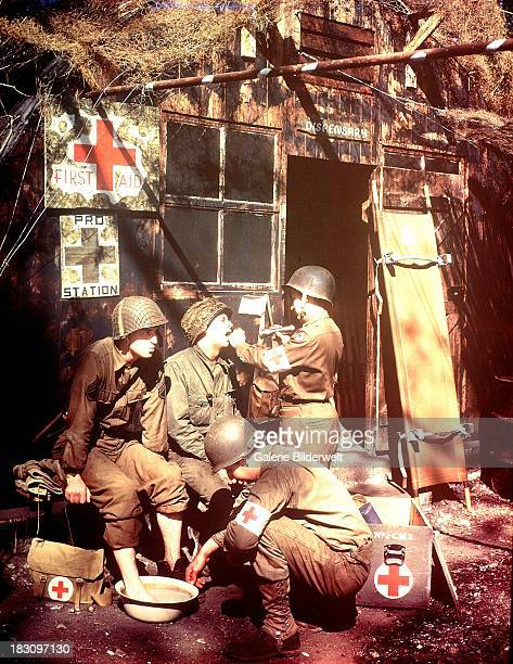 US Army Medics treating two GIs at a first aid post in southern England 1944 The soldiers are among the troops due to embark for the invasion of...