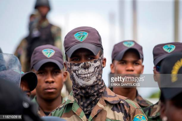 Army members stand guard as supporters of former Dominican President Leonel Fernandez march to the National Congress accusing supporters of Dominican...