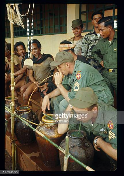 US Army men drinking rice wine from urns as they celebrate Christmas with the Montagnards