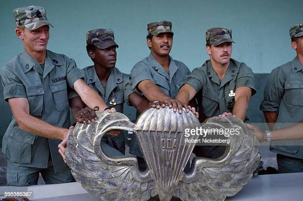 Army military advisors present an oversize brass emblem to the graduating class of a Salvadoran Army parachute group, San Salvador, El Salvador,...