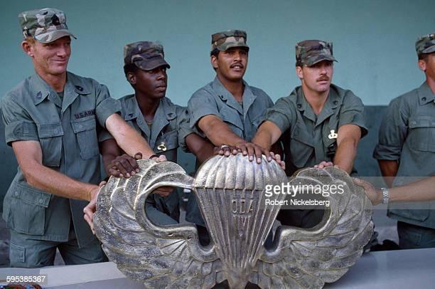 US Army military advisors present an oversize brass emblem to the graduating class of a Salvadoran Army parachute group San Salvador El Salvador...