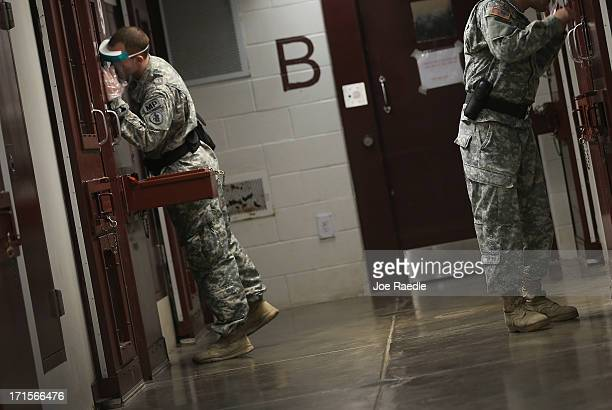 US Army Military Police check on detainees in a cell block during morning prayer at Camp V in the US military prison for 'enemy combatants' on June...