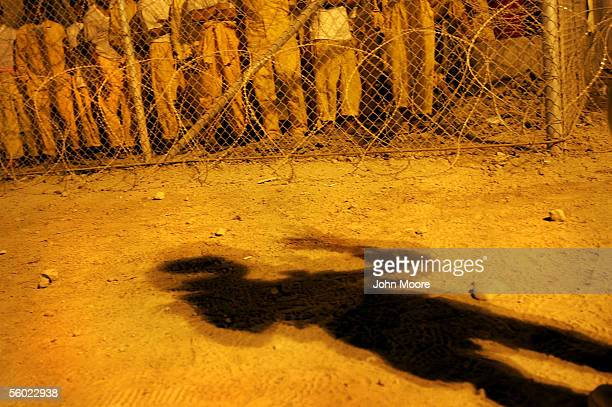 S Army military policeman casts a shadow on the ground as he speaks to juvenile detainees at the Abu Ghraib Prison facility October 27 2005 which is...