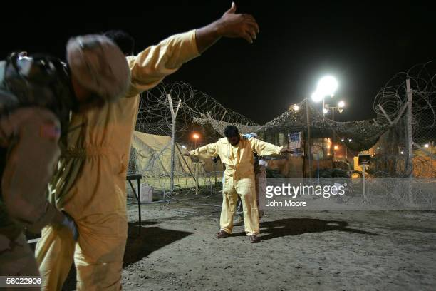 S Army military policemen pat down suspected insurgents while processing new detainees at the Abu Ghraib Prison October 27 2005 in Baghdad Iraq With...
