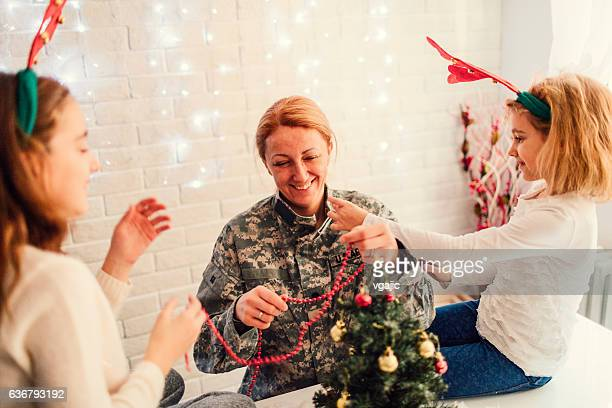army mom decorating christmas tree with her kids. - army christmas stock pictures, royalty-free photos & images