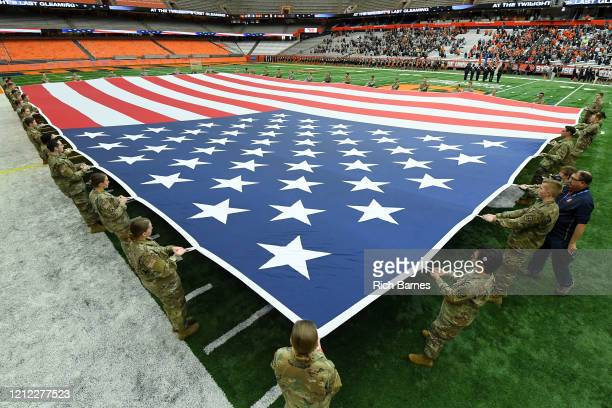 Army National Guard members hold an American Flag during the National Anthem prior to the game between the Army Black Knights and the Syracuse Orange...