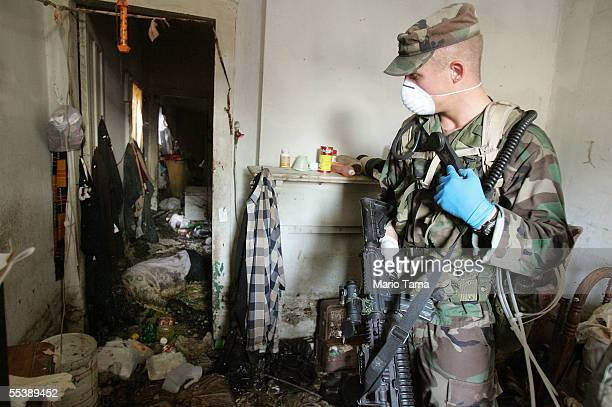 S Army National Guard soldier from Oklahoma wears a mask as a dead body discovered while searching a home lies in the next room September 12 2005 in...