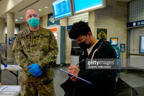 Army National Guard soldier stands by as a traveler registers his travels at the Amtrack Station in Providence, Rhode Island on March 30 during the...
