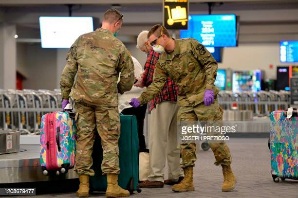 Army National Guard soldiers assist elderly travelers with their luggage at TF Green International Airport in Warwick, Rhode Island on March 30...