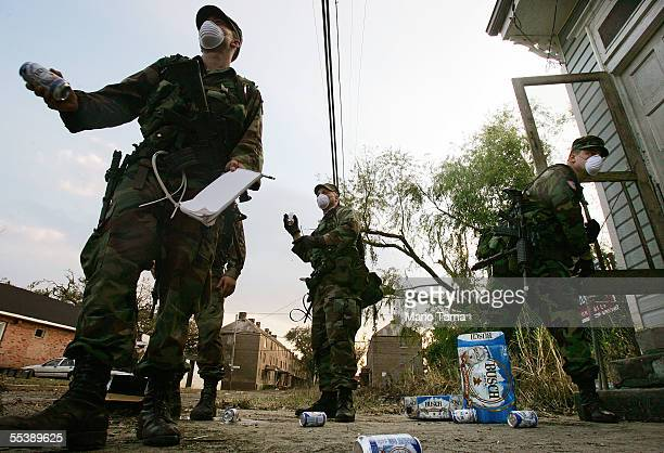S Army National Guard soldiers from Oklahoma throw cans of beer to destroy them while conducting door to door searches September 12 2005 in New...