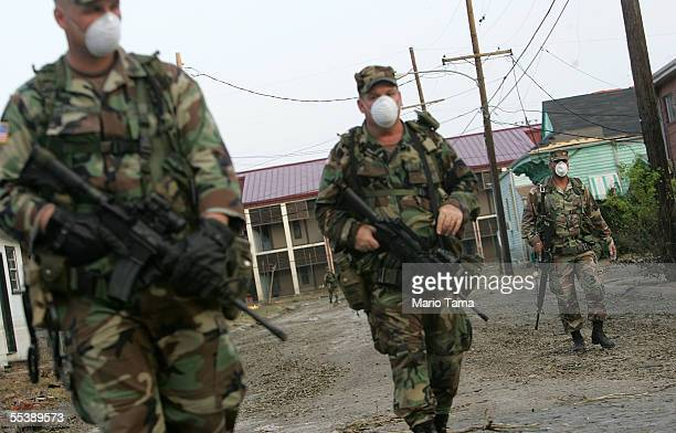 S Army National Guard soldiers from Oklahoma wear masks while conducting door to door searches September 12 2005 in New Orleans Louisiana Rescue...