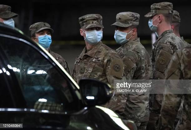 Army National Guard soldiers take a break after loading food into the back of a car at the Kingsbridge Armory, which is being used as a temporary...