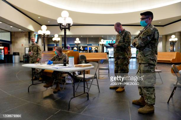 Army National Guard soldiers wait for the arrival of an incoming train at the Amtrack Station in Providence, Rhode Island on March 30 during the...