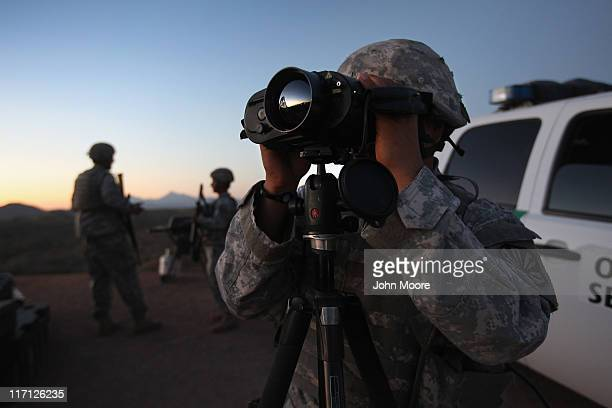 S Army National Guardsman Sgt Oscar Escobar scans the USMexico border at dusk on June 22 2011 in Nogales Arizona The Pentagon recently extended the...