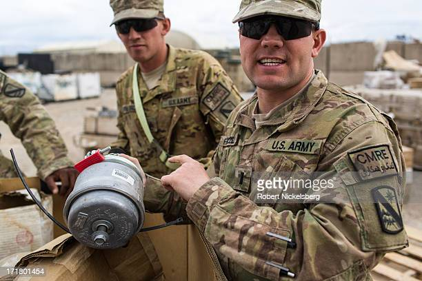 Army officer and logistician holds up a truck part May 4, 2013 delivered from a U.S. Base that has closed at FOB Shank, Afghanistan. Soldiers in the...