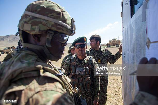 Army officer from the 4th Brigade, 3rd Infantry Division, left, discusses map positions May 6, 2013 with an Afghan National Army commanding officer...
