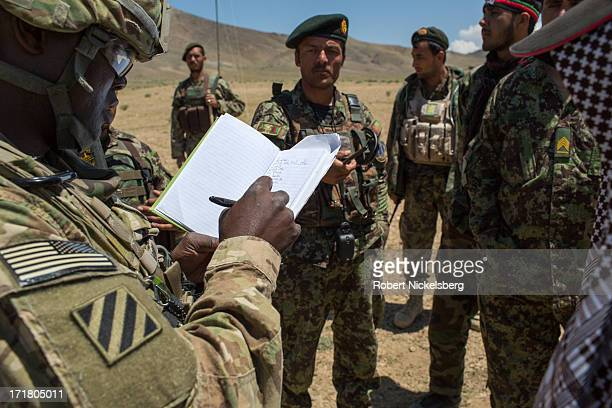 S Army officer from the 4th Brigade 3rd Infantry Division left takes notes May 6 2013 while speaking with a Afghan National Army officer center in...