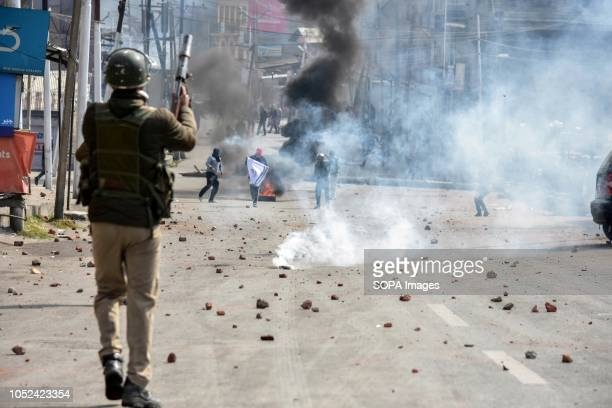 Army officer is seen firing a teargas canister towards the Kashmiri protesters during the clashes Clashes broke out between militants and government...
