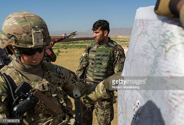 Army officer, left, from the 4th Brigade, 3rd Infantry Division discusses troop locations on a map with officers from the Afghan National Army May 6,...