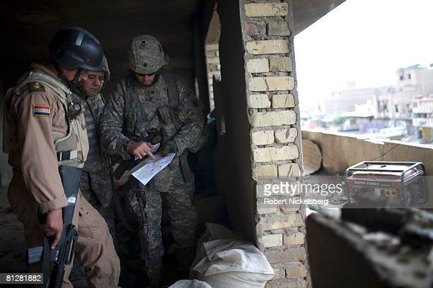 Army officer Lt Col Michael Pembrick center right consults with an Iraqi Army officer left on the front line zone the Iraqi Army controls along the...