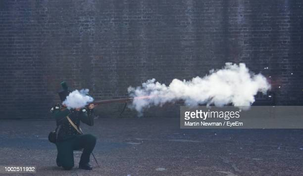 Army Officer Shooting Through Rifle Against Wall