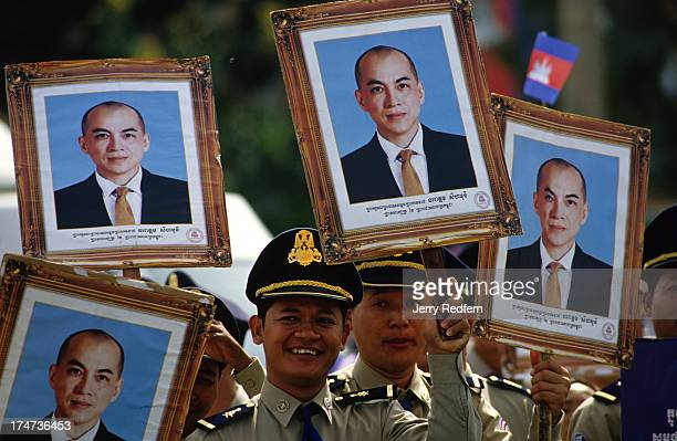 Army officers hold photos of new king Norodom Sihamoni while listening to him speak to the country for the first time following his coronation...