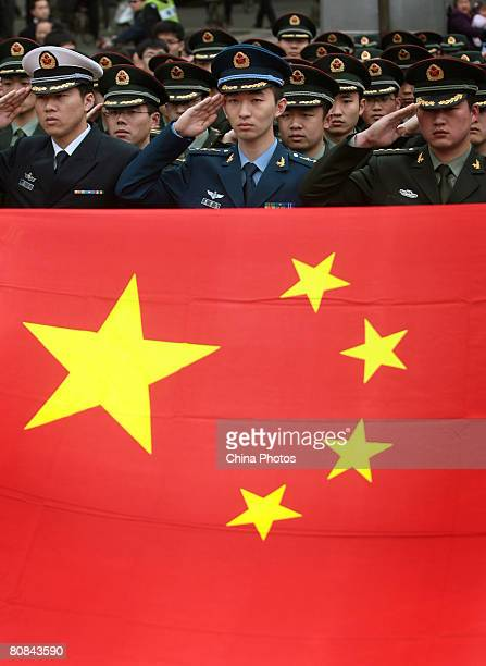 Army officers salute the Chinese national flag in front of the Monument in Memory of the Victorious Crossing of the Yangtze River during a ceremony...