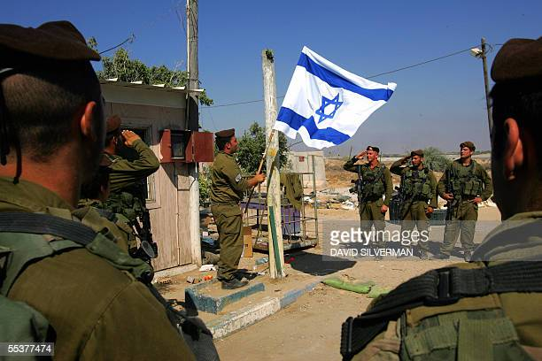 Army officers salutes as Israeli soldiers from the Golani brigade take part in a flag-lowering ceremony as they prepare to withdraw 11 September 2005...