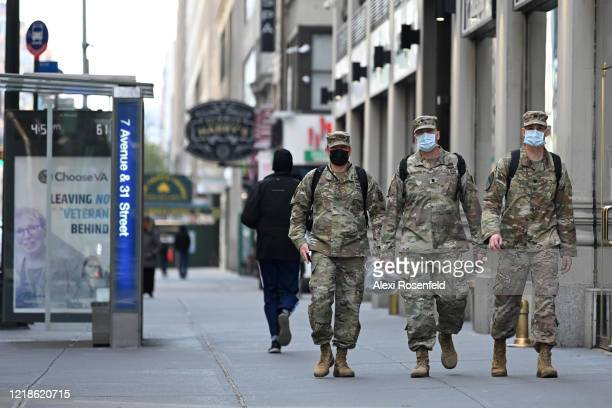Army officers wearing protective masks walk near a sign that reads Leaving No Veteran Behind amid the coronavirus pandemic on April 12 2020 in New...