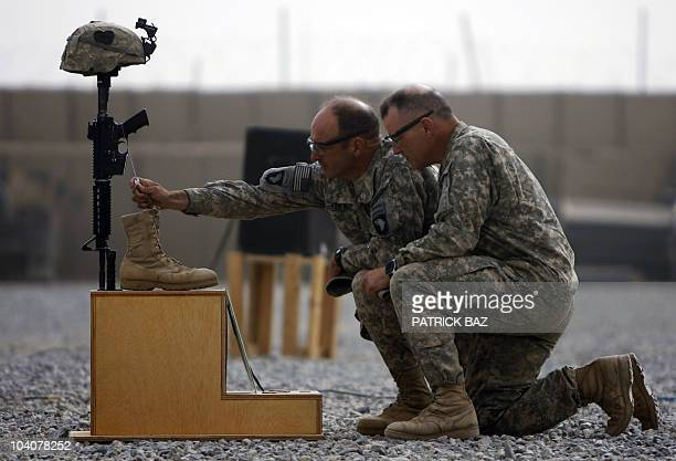 Army officers with the 101st Airborne Division pay their respects by the boots, gun, helmet and dog-tags of US army First Lieutenant Todd W. Weaver...
