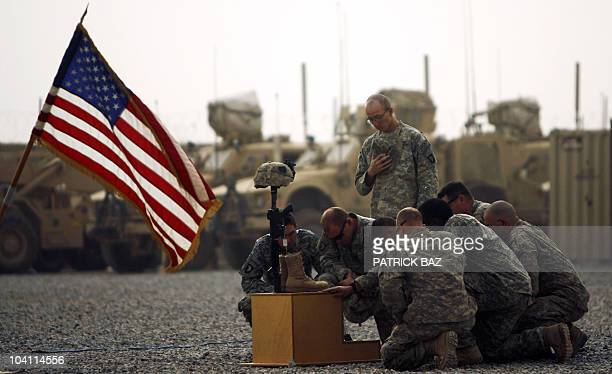 US army officers with the 101st Airborne Division pay their respects by the boots gun helmet and dogtags of US army First Lieutenant Todd W Weaver...